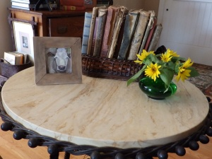 Serendipitous sunflowers accent the gerber daisies; grow to good size; and make a cheerful arrangement beside Ginger Spangler's painting of a cow on an antique table in our living room.